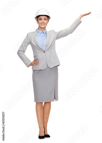 smiling businesswoman in helmet holding something