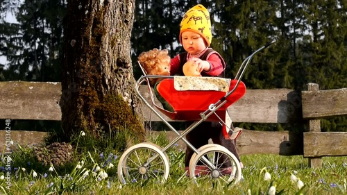 Child playing with doll carriage