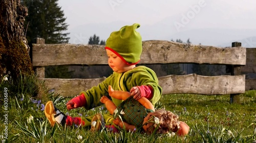 Girl sitting in the garden and playing with a doll