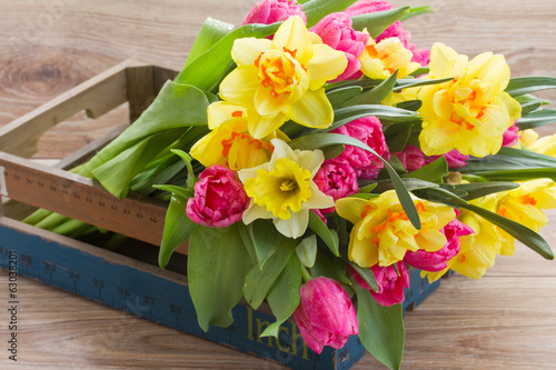 bunch of spring flowers in wooden crate