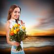 junge Frau mit Blumenstrauß am Strand