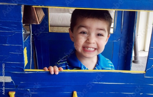 Cute mixed-race boys smiling as he plays in his fort.