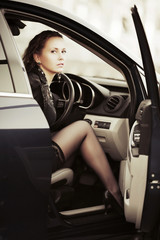 Beautiful young woman sitting in a car