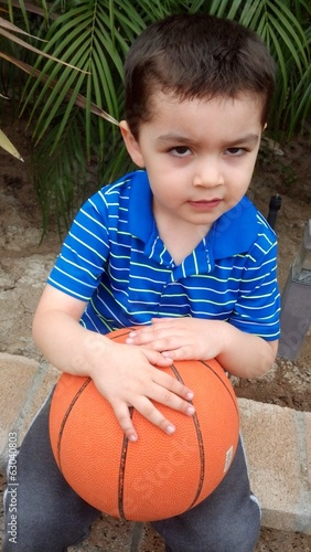 Sad young mixed-race boy waiting to play basketball.