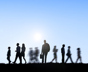 Group of Business People Walking At Sunset