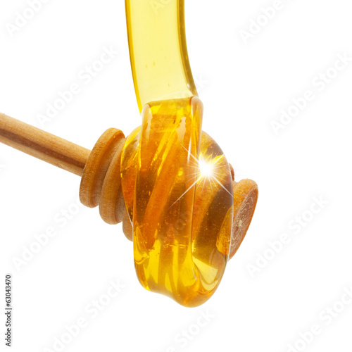 Honey drip from wooden dipper isolated on white background