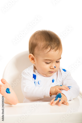 Baby boy with blue paint on hands