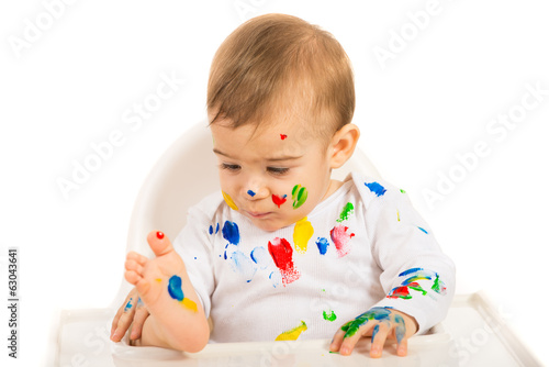 Baby boy looking at colorful paints