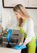 Blonde woman cleaning pipe with cup plunger