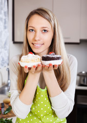 Smiling woman in apron with cakes