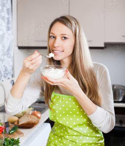 Happy woman eating cottage cheese