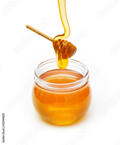 Bowl with honey and wooden dipper on white background
