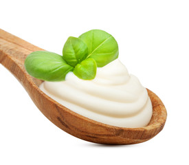 Cream in wooden spoon and basil leaves spice isolated on white