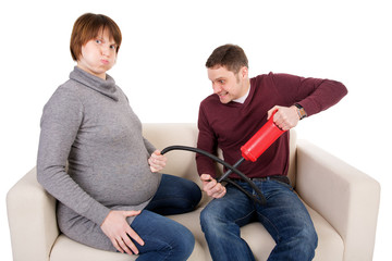 A playful picture of a young couple awaiting baby