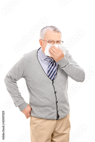 Mature man blowing his nose with