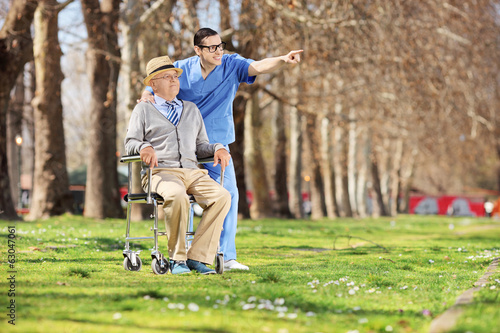Male nurse showing something to a man in wheelchair