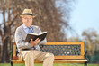 Senior sitting on bench and reading book in park
