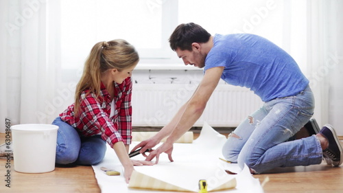 smiling couple cutting wallpaper