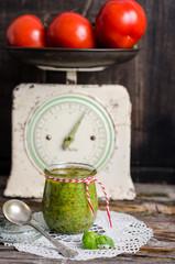 Pesto im Glas und Tomaten auf alter Küchenwaage