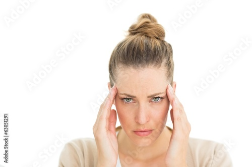 Woman with headache touching her temples looking at camera