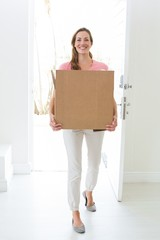 Woman carrying cardboard box in new house