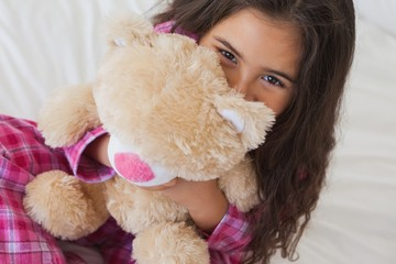 Smiling girl with stuffed toy sitting on bed