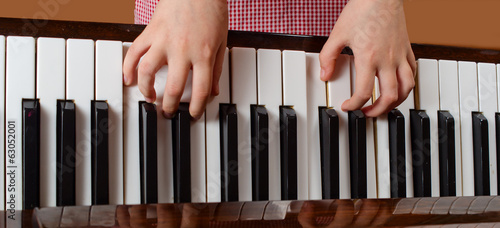 The child learns to play a piano
