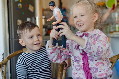 Happy little girl and boy playing with a doll