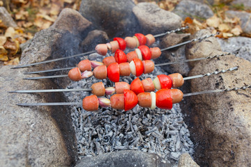 Baked red sausage with garlic, onion and tomatos on grill