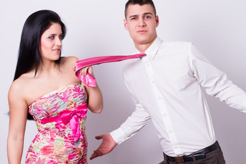 young couple, the woman pulls her boyfriend tie