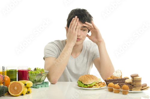 Man choosing between fruits, smoothie,healthy food and sweets