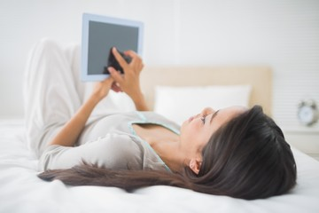 Young girl lying on bed looking at her tablet pc