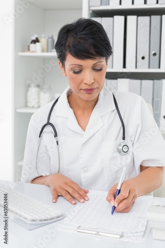 Concentrated female doctor writing on clipboard