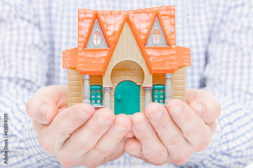 Toy house in hands - 1 to 1 ratio