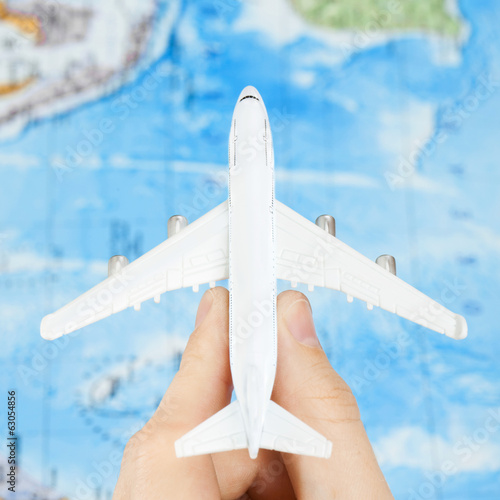Toy aircraft with world map at the background - 1 to 1 ratio