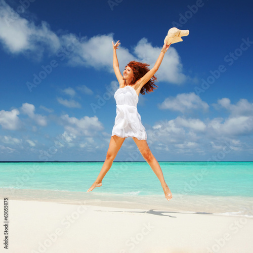 Happy young woman in white dress with hat jumping on the beach