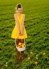 Young woman with basket full of fruits smiling on greenfield of