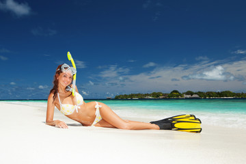 Cute woman with snorkeling equipment relaxing on the tropical be