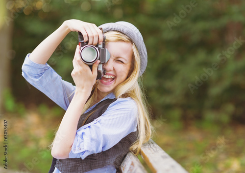 Young hipster taking photo with retro photo camera