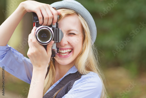 Happy young hipster taking photo with retro photo camera