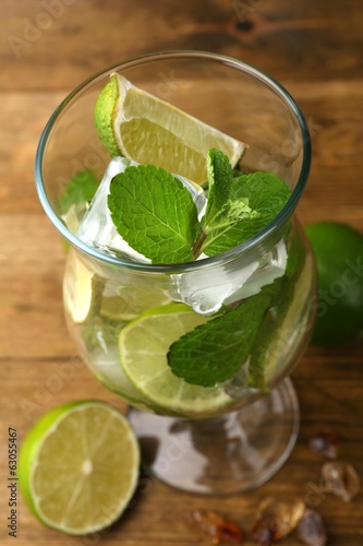 Ingredients for lemonade in glass, on wooden table