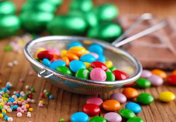 gocce di cioccolato colorate nel colino di metallo