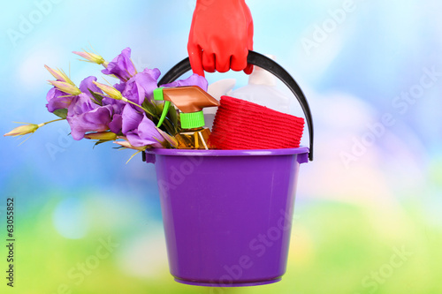 Housewife holding bucket with cleaning equipment