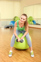 Young woman with gymnastic ball in gym