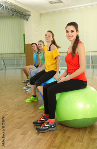 Young beautiful peoples engaged with balls in gym