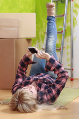 Woman with smartphone in front of moving boxes