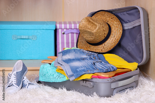 Female clothes in suitcase in room