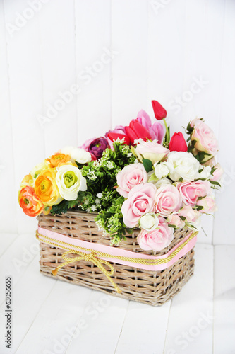 Beautiful flowers in wicker basket, on color wooden background