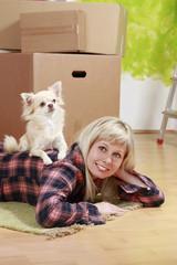 Frau mit Hund vor Umzugskartons