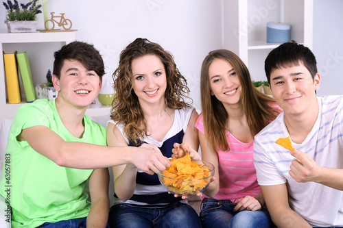 Group of young friends eating chips in living-room on sofa